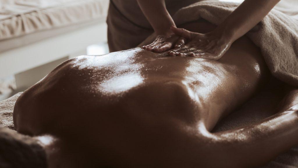 Zweedse relax massage, handen die de rug van een klant masseren met een witte handdoek over de benen